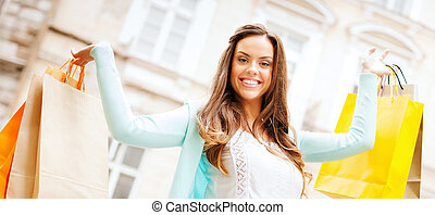 woman with shopping bags in ctiy - shopping and tourism...