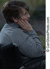 Thoughtful sad senior woman sitting in a wheelchair