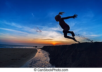 Girl jumping on the sunset beach - Silhouette of the young...