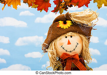 Scarecrow - A scarecrow sitting on fall leaves on a sky...