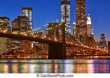 Brooklyn Bridge with lower Manhattan skyline at night -...