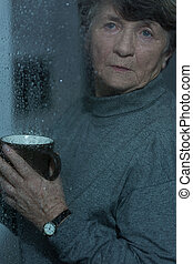 Bad mood in rainy day - Retired woman having bad mood in...