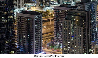 Dubai Marina at night from fooftop, traffic on the road and...