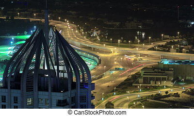 Highway intersection at night with tower from rooftop...