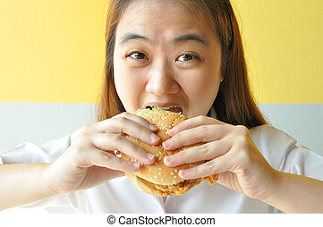 Asian woman age 28 years old in uniform eating chicken burger, j