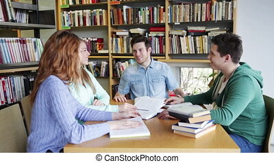 students with books preparing to exam in library - people,...
