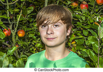 cute smart boy in the garden under the  tree