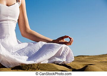 Yoga - Young woman relaxing on the beach