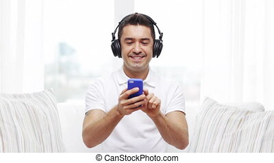 happy man with smartphone and headphones - technology,...