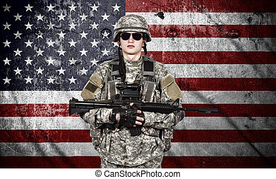 US soldier holding rifle on a american flag background