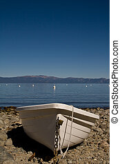 Row boat - Single plastic boat beached on rocks, lake in...