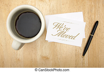 Weve Moved Note Card, Pen and Coffee Cup on Wood Background...