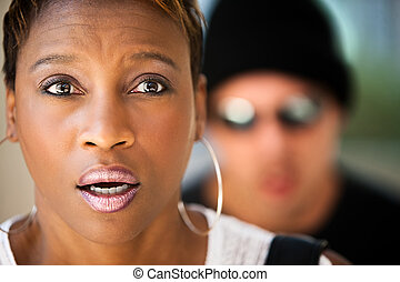 Woman being stalked by criminal in sunglasses and ski hat