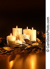 White candles with gold leaf garland on dark background