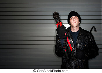 Burglar with Crowbar - Young burglar in leather jacket with...