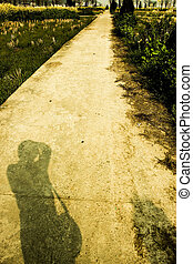 Field road and shadow of man on the road