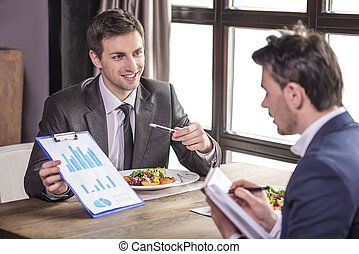 Business lanch - Smiling businessmen analyzing graphs during...