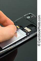 Male hand inserting Micro SD card to mobile phone