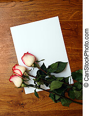 roses and blank paper on table