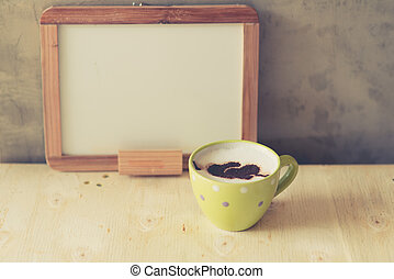 Cup of coffee with white board on wooden table.