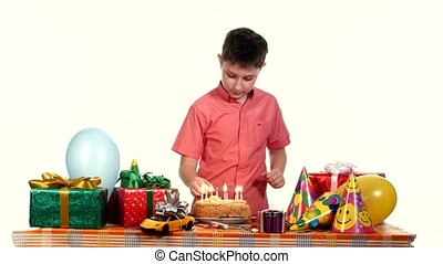 Boy lights candles on his birthday cake. Table strewn with gifts and balloons. white background