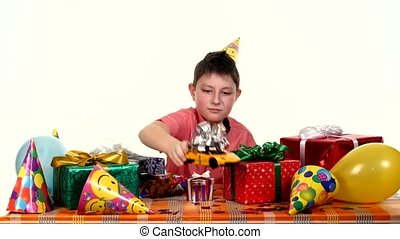 Birthday boy sitting at a small table with gifts and treats yellow car