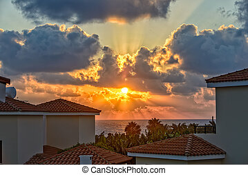 Sunset over holiday beach villas on Cyprus coast