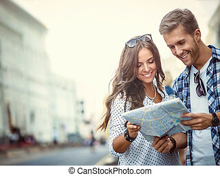 Vacations - Smiling couple with a map outdoors