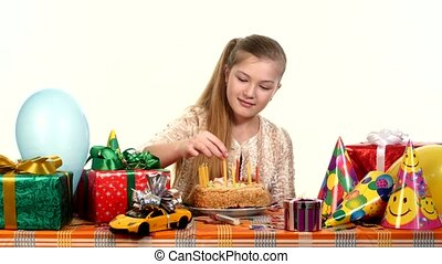 Girl sitting at banquet table. It is faced cake with candles. scattered around gifts