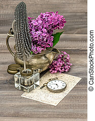 lilac flowers and antique inkwell on wooden background retro...