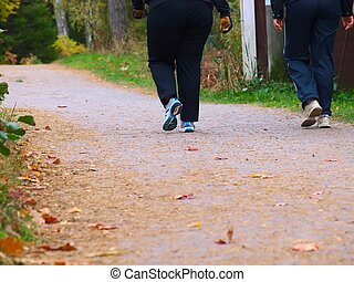 2 people walking - A couple of people walking on a gravel...