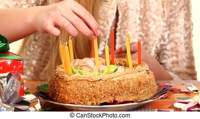 Girl decorate a birthday cake, cake scattered around gifts...