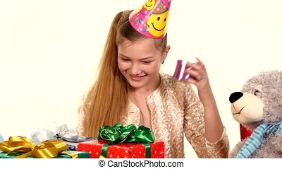 Birthday girl sitting at the table sees boxes with gifts and...