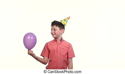 boy in cap lets air balloon white background. slow motion