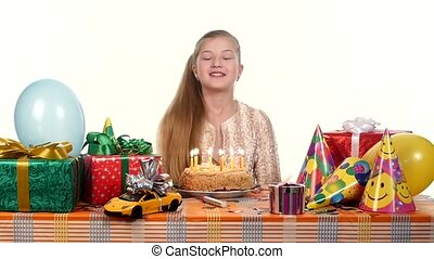 Girl decorates a cake with candles, sitting at the table. Gifts scattered around her. slow motion
