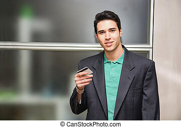 Handsome young man in office holding a credit card
