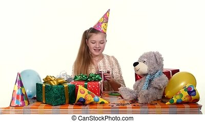 Birthday girl sitting at the table considers all their boxes with gifts, opens one of them