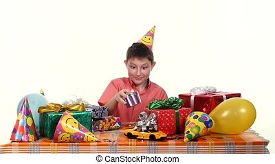 Birthday boy sitting at small table and chooses gift him to open. slow motion