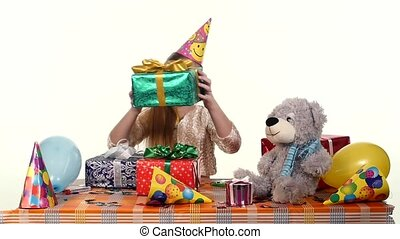Birthday girl sitting at the table considers all their boxes with gifts, her high spirits
