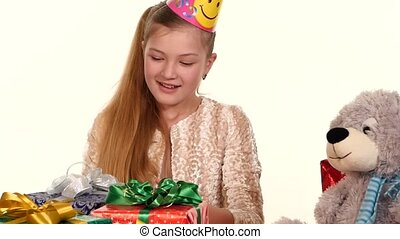 Girl in cap sitting at festive table and considers all their gifts. slow motion