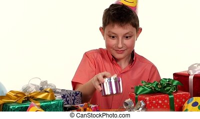 Boy examines all his gifts received birthday, he wants to know that in each box