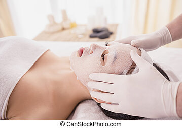 Spa therapy for young asian woman receiving facial mask at...