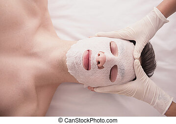 Spa therapy for young male receiving facial mask at beauty...