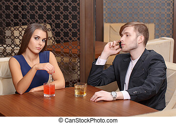 Couple sits in the cafe - Doing business. Young man talking...