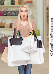 Girl holds shopping bags in her hands - Oh my god. Scared...