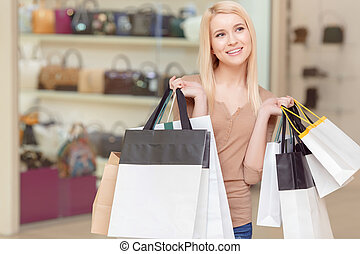 Girl holds shopping bags in her hands - Happy shopping....