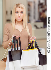 Girl holds shopping bags in her hands - Puzzled with the...