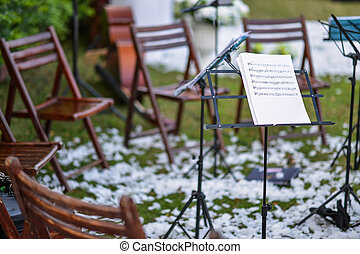 Music stand and empty chairs in the garden