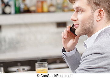 Young man talks over the phone - Arranging a meeting in the...