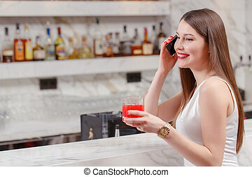 Woman speaks over the phone in bar - Friendly phone...